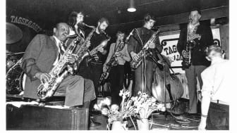 "From left to right: Ben Webster, Holger Laumann, Finn Odderskov, unknown baritone saxophonist, Jesper Thilo and Dexter Gordon. Location: ""Jazzhus Tagskægget"" in Aarhus (1967-73)."