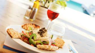 Omgivelserne betyder meget for vores lyst til at spise anderledes på ferien. En græsk salat med lammekoteletter og oliven gør sig godt på en græsk taverna.