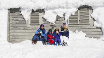 Familj njuter på fjället -vårvintern