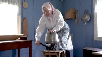 Anno Odalstunet formidler bruk av gjenstandene i museets samling. Birgitta Andreassen demonstrerer kjerning (kjinning) av smør. Foto: Anna Løvlund
