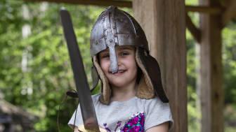 Barn som leker med vikingsverd og vikinghjelm på Midgard vikingsenter