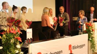 Johan Lindholm, ordförande i Riksbyggen, delar ut blommor till stipendiaterna.