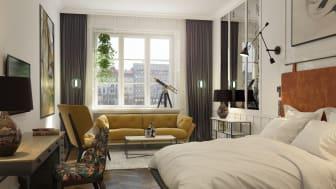 Ajattoman tyylikkäiden huoneiden sisustuksessa on käytetty lämpimiä värisävyjä sekä ripaus trendikkyyttä. Pehmeä, leveä vuode on huoneen keskipiste.