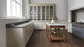 Real Classic Karleby-køkken med håndmalede asketræslåger i den nye farve Mandel. Lågerne har dobbelt perleliste og messing- eller bronzegreb. De høje vitrineskabe er forsynet med nye rillede glas. Bordpladen er i kalksten fra Killekulle.