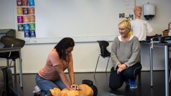 Tina Miller (th.) instruerer en af eleverne på Tradium i førstehjælp på en af de nyindkøbte træningsdukker.
