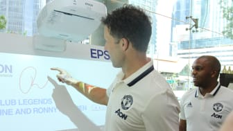 (From left to right) Manchester United legend Ronny Johnsen signing on the Epson EB-1430W interactive, ultra-short-throw projector with legend Quinton Fortune beside him.