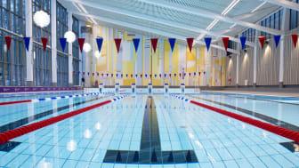 Åkeshovs sim- och idrottshall. Den helt återställda 25-meters bassängen samt fondmålning av av konstnären Lasse Andréasson.
