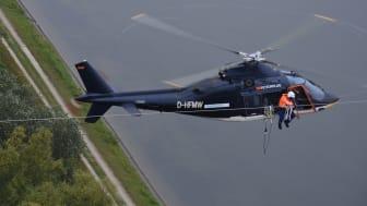 Aus dem Hubschrauber heraus montiert eine Spezialfirma am Donnerstag, 16. Juli, im Auftrag der Bayernwerk Netz GmbH Vogelschutzmarkierungen auf einer Hochspannungsleitung in Ingolstadt. Foto: Günter Drewnitzky