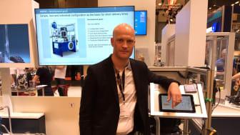 Jens Lindfeldt visar en hydraulpump med Condition Monitoring i bakgrunden.