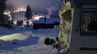Inlandsbanans klassiska motorvagn av modell Y1 står parkerad i ett kyligt och storslaget vinterlandskap.