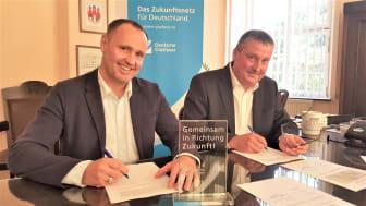 Gemeinsam in Richtung Zukunft: Michael Kölling, Regional Manager Deutsche Glasfaser und Stefan Müller, Bürgermeister der Stadt Trebsen bei der Unterzeichnung des Kooperationsvertrages. (DG)
