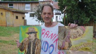 """Udo-Lindenberg-Fan Jörg Ernst Brück in seinem Lieblings-T-Shirt zeigt zwei seiner in Holzbrandtechnik geschaffenen Bilder von """"Panik-Udo"""" und Keith Richards."""