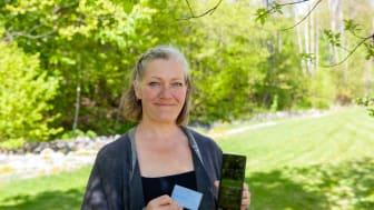 Anita Vasstveit med sitt første utfylte Donorkort™ og den nyeste appen på telefonen.