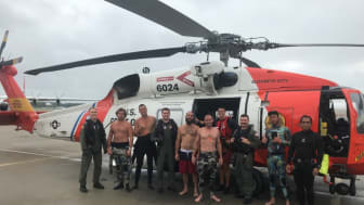 US Coast Guard Fifth District Command Center personnel with the fishermen saved this summer off Cape Henry. Credit: USCG