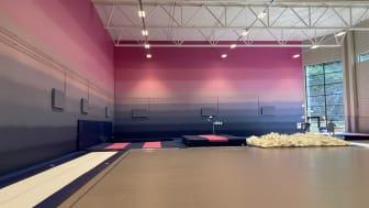 Hall för truppgymnastik med högt i tak och särskild färggradering på väggen, för gymnasternas möjlighet att orientera sig i luften.