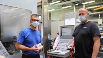 CNC-Fräser Martin Dörrbecker (links) und CNC-Dreher Jens Kühn präsentieren die in der Hephata-Werkstatt für Menschen mit Behinderungen in Schwalmstadt-Ziegenhain gefertigten Teile.