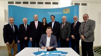 Michael Dümig von der Kommunalen Allianz Westspessart unterschreibt die Kooperationsvereinbarung im Beisein von Finanz- und Heimatminister Füracker (3. v.l.), Deutsche Glasfaser CEO Uwe Nickl (5. v.l.) und weiteren Vertretern der Allianz und DG.