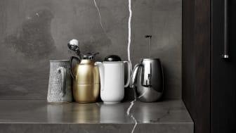 Den røgede eg får klædeligt selskab af en 40 mm tyk marmor i en grå nuance med hvide åretegninger, som fortsætter fra bordpladen op ad væggen.