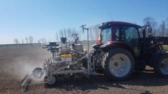 Traktor sprider den torkade växtnäringen