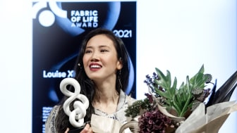 Louise Xin tar emot Fabric of Life Award