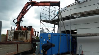 Das erste Blockheizkraftwerk für die Wärmezentrale der Springbach Höfe wird vorsichtig in das Gebäude eingesetzt.