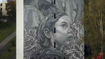 Kolme taloyhtiön asukasta antoi kasvonsa seinämaalaukseen. Kuva Paola Delfin