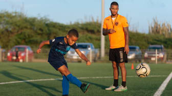 A young boy playing football as his coach observes