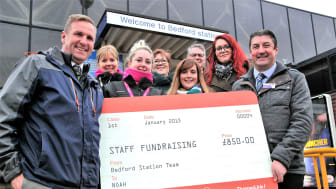 Jim O'Connor MBE, NOAH Enterprise Chief Executive (left) accepts the £850 donation from Bedford Station Manager Joe Healy (right) and the Thameslink bake sale team