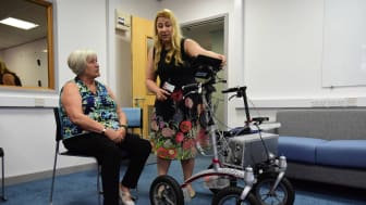 Volunteer Pauline being shown how to use the robotic walker by researcher Mia Campbell from Northumbria's PaCT Lab