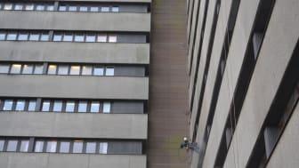 Reparbetare från Klätterservice arbetar sig systematiskt nedåt utrustade med högtryckstvättar.
