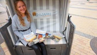 Marketingmitarbeiterin Lina Rotte stellt die neue Urlaubsbroschüre und das Gastgeberverzeichnis für die kommende Saison vor ©Tourismus-Service Fehmarn