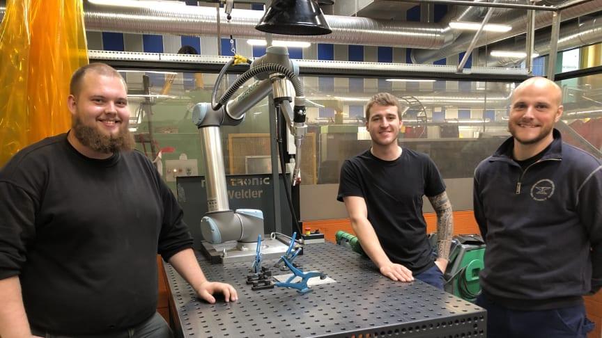 Smedelærlingene Mikkel, Alexander og Nicky med den kollaborative robot, CoWelder