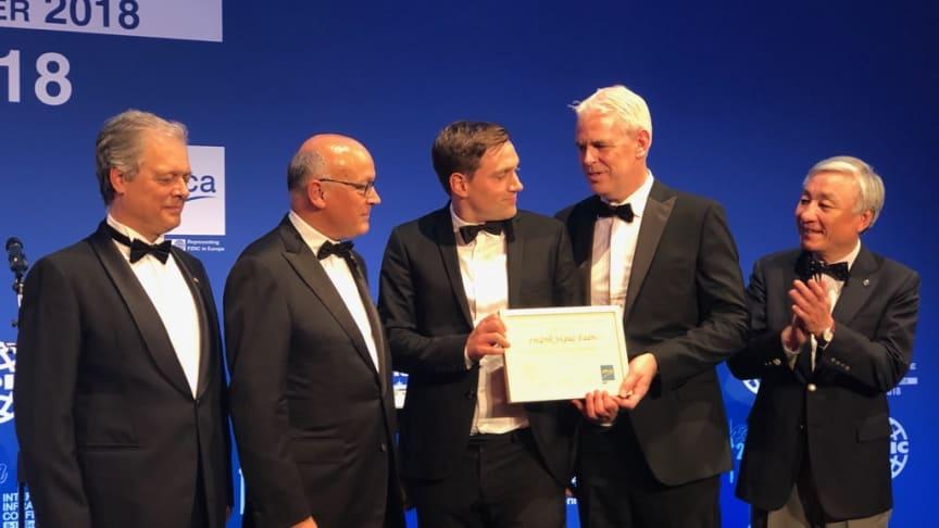 Norconsults Fredrik Skaug Fadnes (midten) mottar prisen for andreplass i EFCAs årlige Young Professionals-konkurranse. Foto: RIF