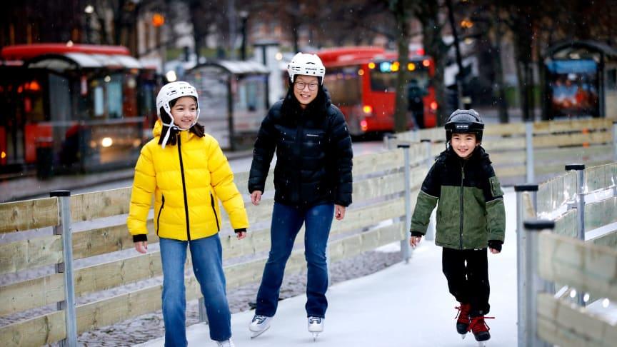 Kvinna och två barn åker skridskor på isbanan på Stora Torget.