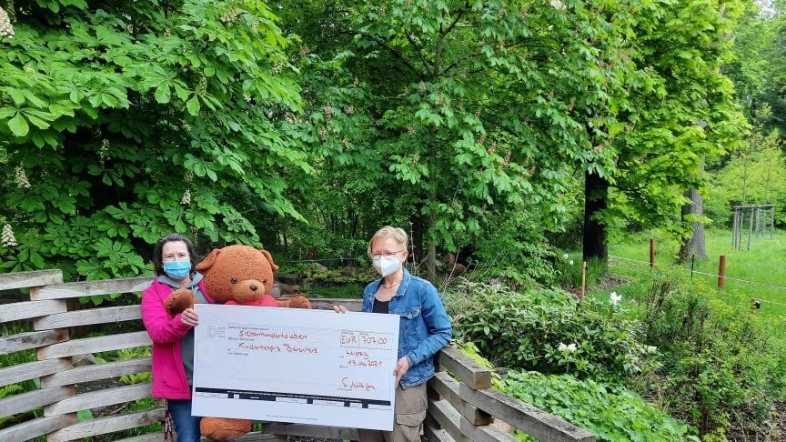 Kerstin Stadler und Sabine Müller-Gora präsentieren den Spendenscheck im Bärenherz-Erinnerungsgarten