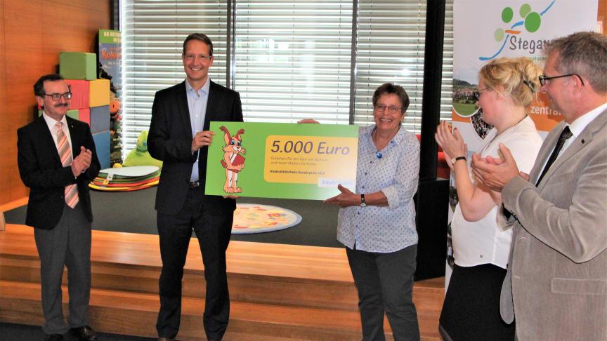 Den Kinderbibliothekspreis überreicht Ingo Schroers vom Bayernwerk an Bibliotheksleiterin Cornelia Kempgen (mi.). Pfarrer Walter Ries (li.), Dr. Claudia Pecher vom St. Michaelsbund (2. v.r.) und Bürgermeister Thilo Wagner gratulieren.