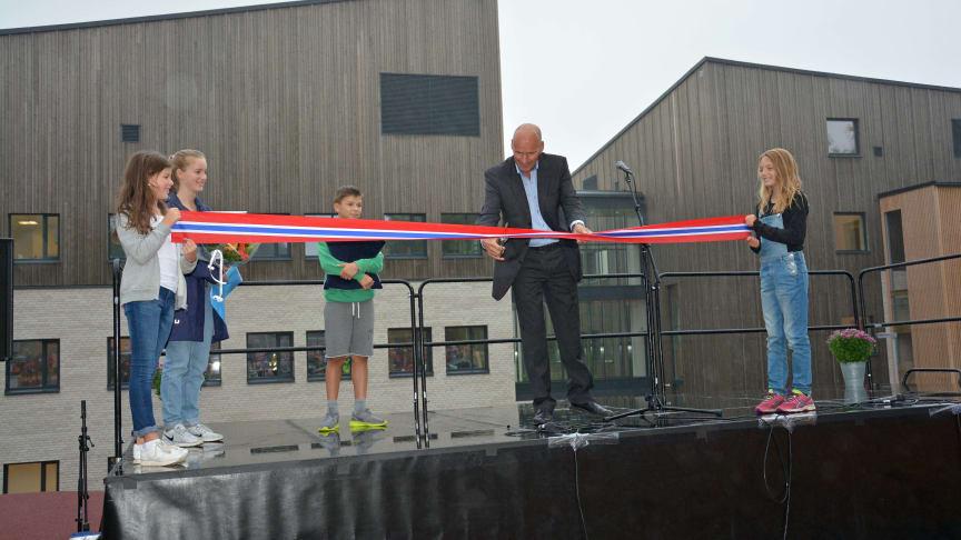 Byråd Geir Lippestad klipper snoren under åpningen av nye Munkerud skole i godt samarbeid med elever.