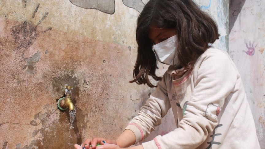 Tala, 9 år och från Syrien, tvättar sina händer för att minska risken för virusspridning.