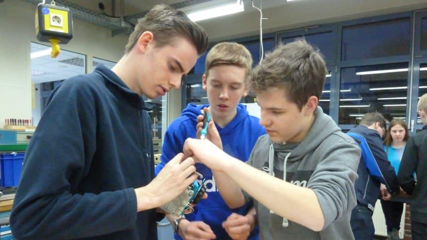 WWE- Azubi Mark Hindersen, Jonas Oehler und  Raphael Kolax von der Gesamtschule Rödinghausen  bauen einen Mini-Roboter in der Ausbildungswerkstatt in Kirchlengern (v. l.).