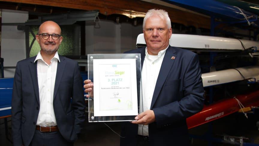 Der Vereinsvorsitzende des Rudervereins, Carsten Heinemeyer (r.) nimmt die Sieger-Urkunde von Andreas Speith, Geschäftsführer bei Westfalen Weser, entgegen..