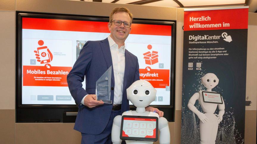 Vorstandsmitglied Dr. Bernd Hochberger mit dem Digital Award und Roboter Monaco Pepper