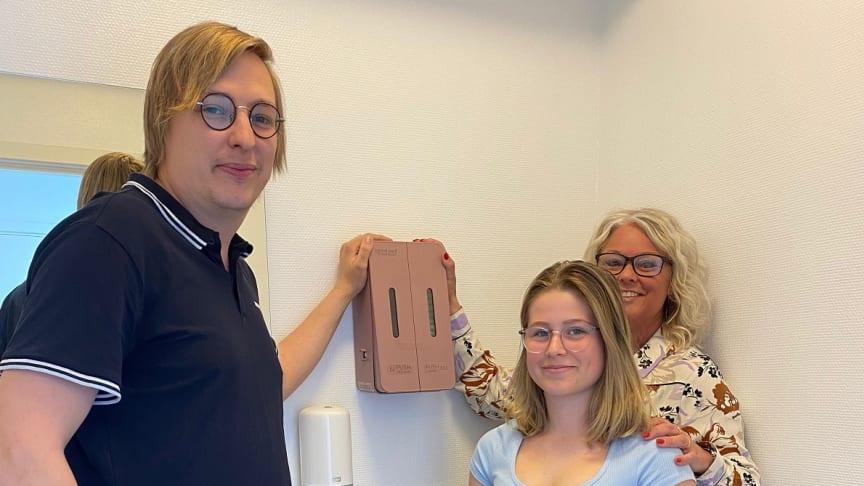 Svenskaläraren Joel Crona och rektorn Anne Henrichson, Thoren Framtid Hässleholm, flankerar Tilda Bondesson som via sin debattartikel fick skolan att köpa in gratis mensskydd.