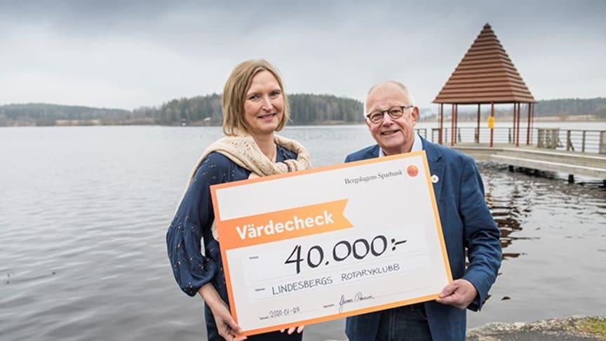 Leif Ohlsson, president i Lindesbergs Rotaryklubb tar emot check av kontorschef Yvonne Persson.