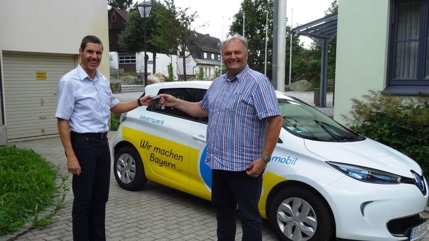 Bayernwerk-Kommunalbetreuer Burkhard Butz (l.) übergibt den Schlüssel eines voll elektrischen Renault Zoé aus dem Bayernwerk-Fuhrpark an Fichtelbergs Bürgermeister Georg Ritter (r.).