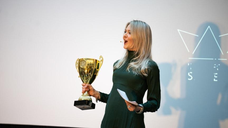 konferencier Elsa Landberg håller i vinnarpokalen från Hack for Swedens Hackathon 2018