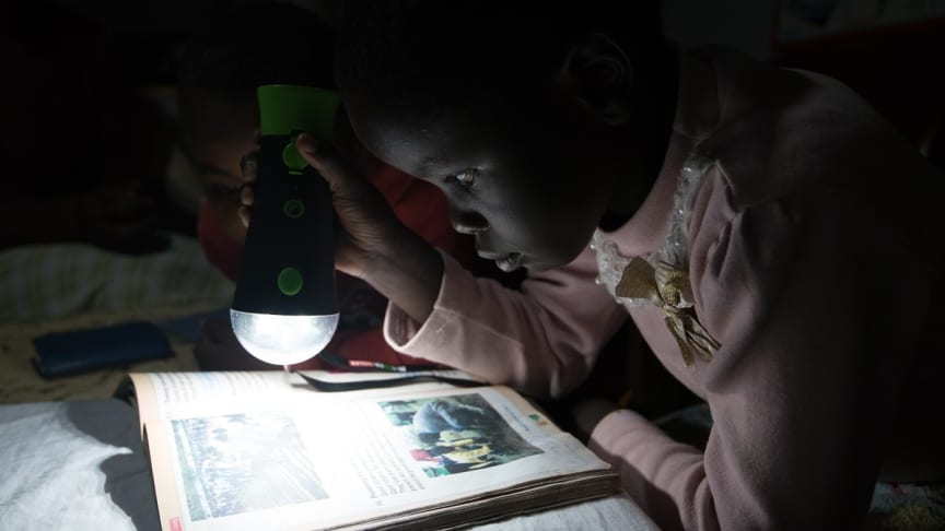 A child in Kenya is reading in the light from off-grid solarenergy. SunFunder borrower [Questworks / M-KOPA], Kenya