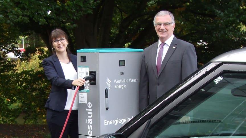 Christiane Rüsel, Kommunalreferentin bei Westfalen Weser, und Bürgermeister Klaus Hülsenbeck testen die E-Ladesäule in Marsberg.
