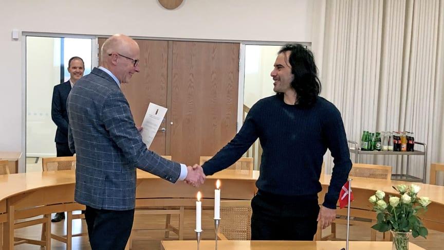 Billedtekst 1: Ilia Amini, der bor i Vejen, var den første til at skrive under. I baggrunden ses viceborgmester Morten Thorøe.  Foto: Vejen Kommune.