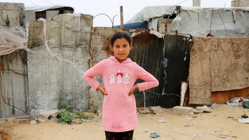 Ruba, 10 år, från Gaza står utanför det skjul som hon och hennes familj var tvungna att flytta till efter att deras hus blev bombat.