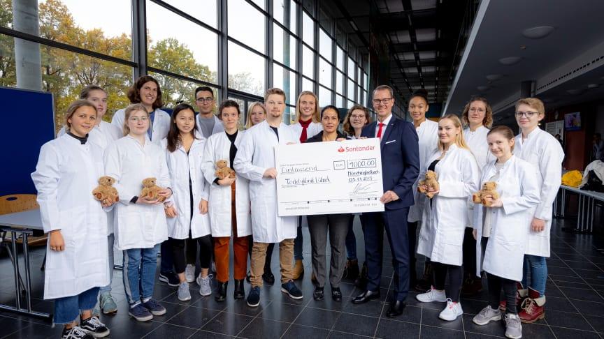 """Filialleiter Volker Giering überreichte den Scheck über 1 000 Euro gemeinsam mit seiner Kollegin Daniela La Ferrera symbolisch im Namen von Santander an die Lübecker Medizinstudenten, die sich im Projekt """"Teddyklinik"""" engagieren"""